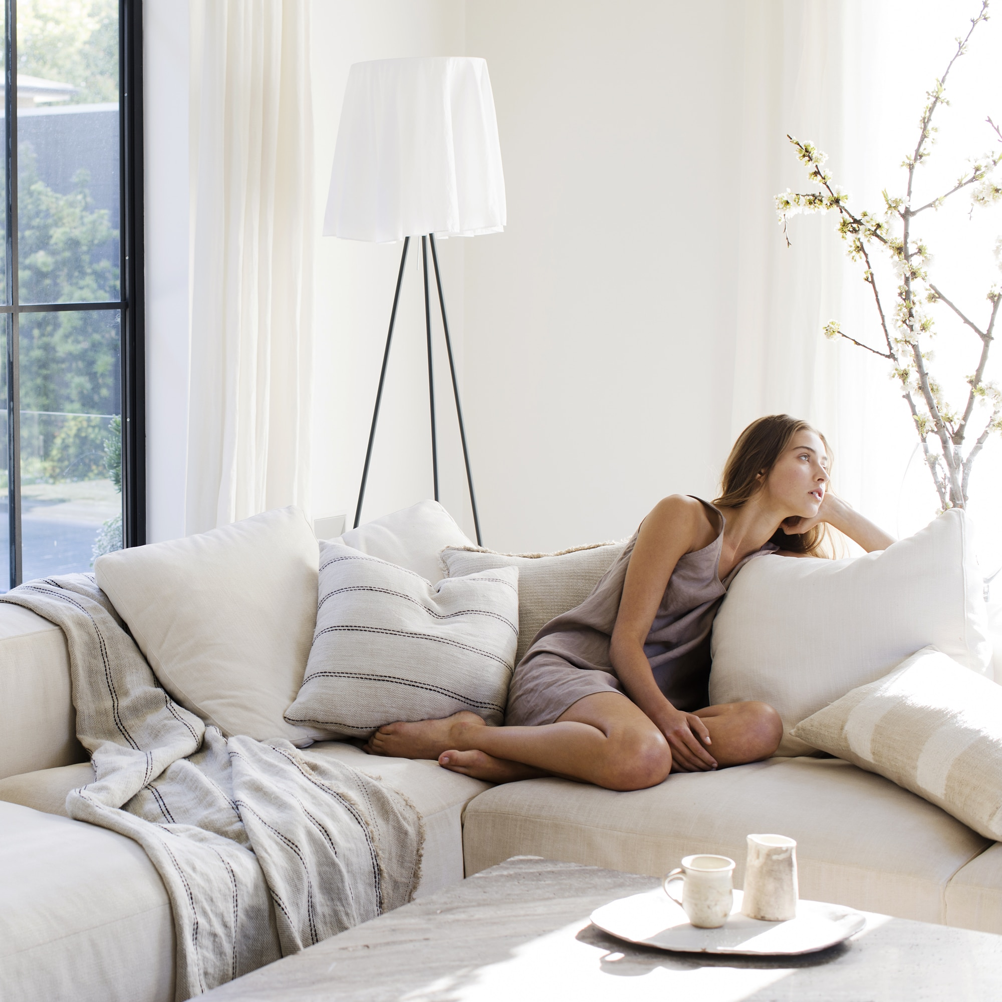 Ana cushion and throw on the lounge with model from Monsoon Living Newcastle